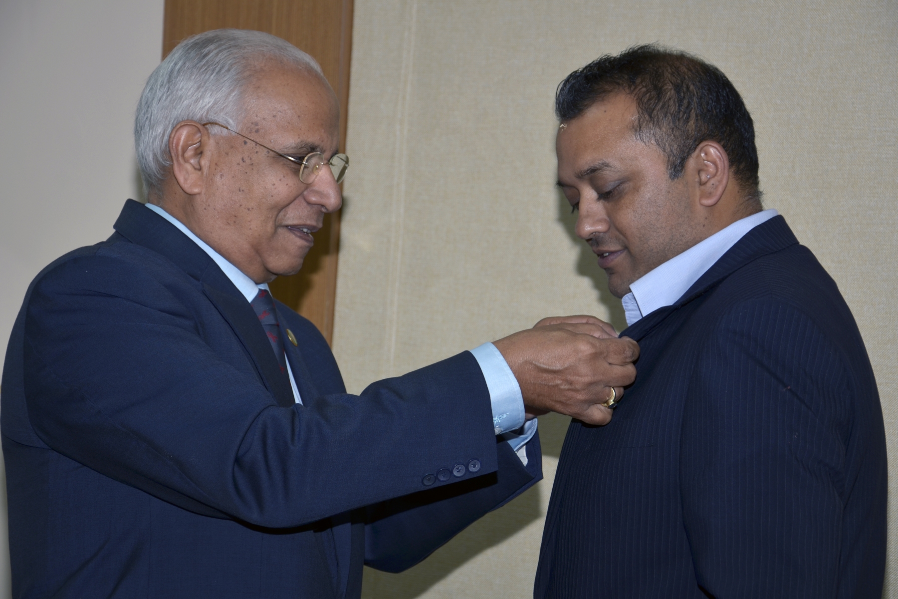 United Nations Secretary-General's Special Envoy for AIDS in Asia and in the Pacific, J.V.R. Prasada Rao pins a red ribbon on the jacket of the Minister of Health of Nepal, Gagan Kumar Thapa